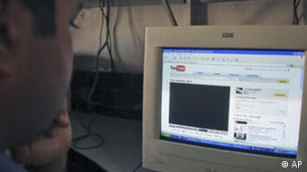 A man looks at a blocked YouTube page on a computer screen