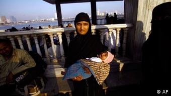 A Muslim woman holds her child and stands at the Haji Ali Dargah in Mumbai (Photo: Rafiq Maqbool/AP/dapd)