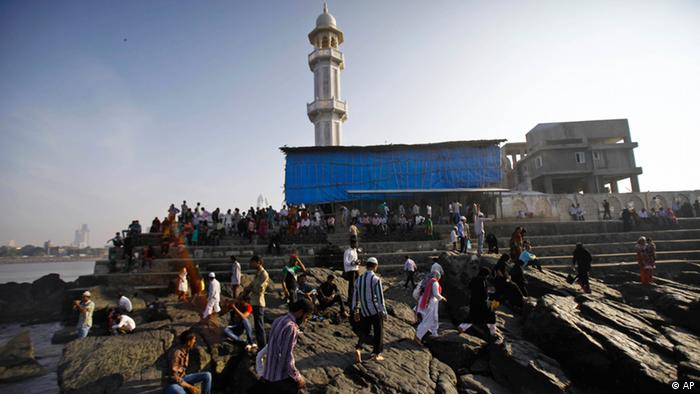 Indians relax on rocks on the shores of the Arabian Sea next to the landmark Haji Ali Dargah in Mumbai, India (Photo: Rafiq Maqbool/AP/dapd)