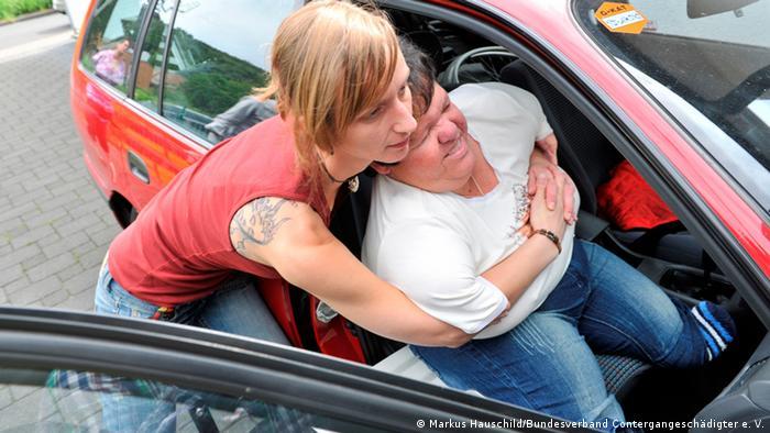 Eine Frau hilft einer Frau ohne Arme aus dem Auto.