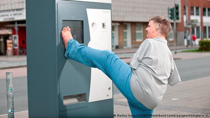 Ein Mann bedient einen Parscheinautomat mit dem Fuß (Foto: Markus Hauschild/ Bundesverband Contergangeschädigter e. V.)