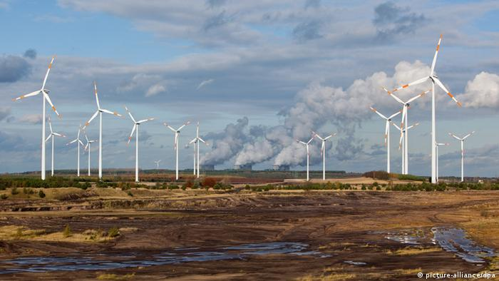 Wind turbines in front of the cooling towers of a coal-fired power station Photo: Patrick Pleul dpa/lbn