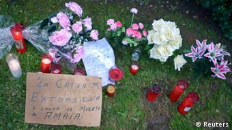 A card, candles and flowers lie close to where Amaia Egana, a 53-year-old woman, threw herself out of her fourth-storey apartment window in Basque Country as court officials came up the stairs to evict her on Friday, in Barakaldo November 10, 2012. The card reads La Caixa (bank) extorts and causes the death of Amaia. Spain's Prime Minister Mariano Rajoy said on Friday that the government would introduce measures to protect families from eviction for non-payment of mortgages. REUTERS/Vincent West