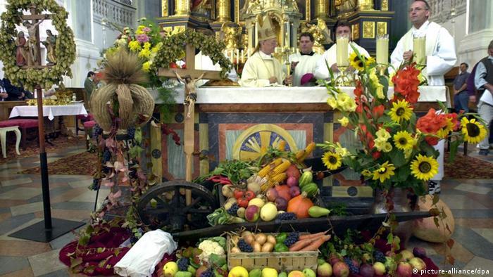 Priester stehen am 1.10.2000 vor dem festlich geschmückten Altar der St. Anna Basilika in Altötting (Oberbayern). Traditionell feiern die Katholiken das Erntedankfest, zu dem die Kirchen mit Blumen und Getreide ausgeschmückt werden.