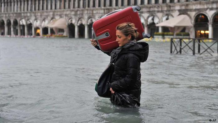 A tourist carrying a suitcase on her left shoulder crosses flooded St. Mark's Square in Venice, Italy, Sunday, Nov. 11, 2012. Photo: AP Photo/Luigi Costantini