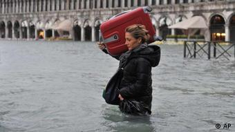 Hochwasser auf dem Markusplatz in Venedig. Eine Fußgängerin trägt ihren Koffer durchs Wasser (Foto: AP).