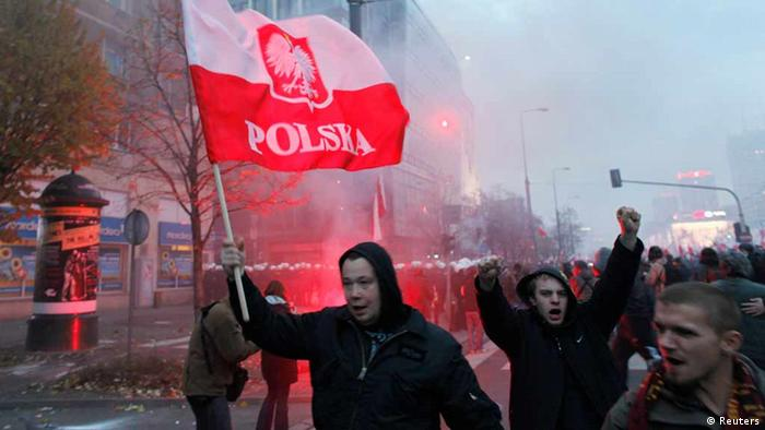 A demonstrator holds up a flag as violence breaks out at a parade celebrating Poland's national holiday (Photo: REUTERS/Peter Andrews)