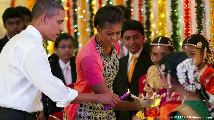 US President Barack Obama (L) and First Lady Michelle Obama (C) light Diwali candles during a cultural event at The Holy Name High School in Mumbai on November 7, 2010. Barack Obama's Asia trip has turned into an early test of whether the US president's global goals and prestige will survive his weakened grip on domestic power, following a painful rebuke from voters. In India, Indonesia, South Korea and Japan, Obama is trying to pull off the trick of advancing a still ambitious foreign policy, while reducing high unemployment left barely touched by the sluggish economic recovery. AFP PHOTO/Jim WATSON (Photo credit should read JIM WATSON/AFP/Getty Images)