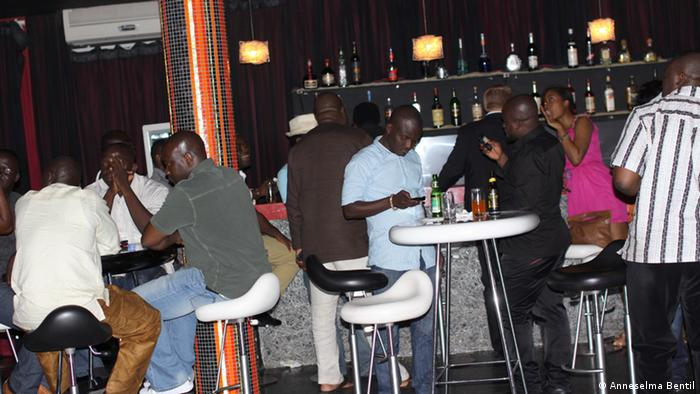 Patrons at Citizen Kofi in Accra, Ghana stand at the bar, ordering drinks