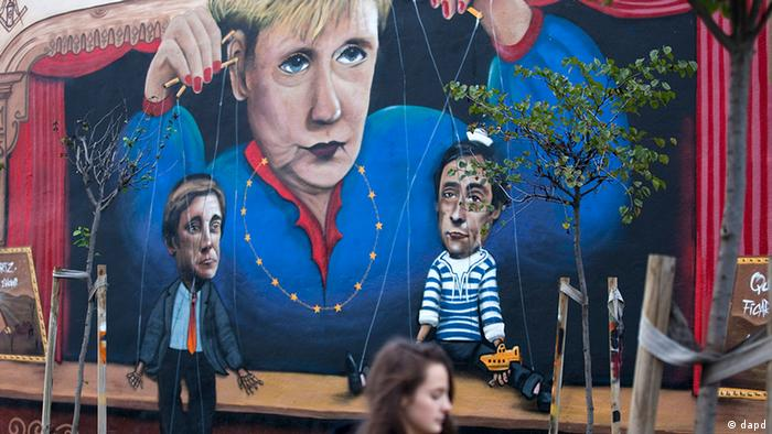 A girl walks past a graffiti in Lisbon showing German Chancellor Angela Merkel as a puppeteer controlling the Portuguese prime minister and foreign minister (Foto:Armando Franca/AP/dapd)