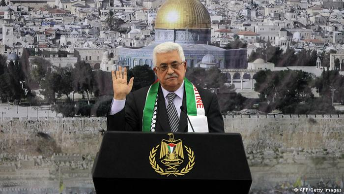 Palestinian President Mahmud Abbas gestures as he delivers a speech to mark the eighth anniversary of the death of the late leader Yasser Arafat, in the West Bank city of Ramallah on November 11, 2012. Palestinians are coordinating with Russia, as well as Swiss and French experts, on the exhumation of Arafat who died in a French military hospital near Paris on November 11, 2004, and who French experts were unable to say what had killed him. Many Palestinians are convinced he was poisoned. In the background is an image of Jerusalem's Dome of the Rock in the al-Aqsa compound, Islam's third most holiest site. AFP PHOTO/ABBAS MOMANI (Photo credit should read ABBAS MOMANI/AFP/Getty Images)
