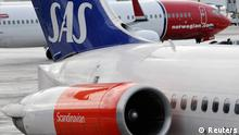 File photo of Norwegian Air's Boeing 737-800 aircraft preparing for takeoff behind a SAS MD-82 aircraft parked at gate on Terminal 5 at Arlanda airport, north of Stockholm February 9, 2010. Loss-making airline SAS will shed nearly 6,000 staff through cuts and asset sales to secure loans from banks and Nordic governments to help it survive a global downturn and fierce competition. SAS, one of the European flag-carriers being squeezed by discount carriers such as Ryanair and Norwegian, has not made a full-year profit since 2007. Without the loans, SAS might have to stop flying. Announcing its new savings plan November 12, 2012, it said it expected a slight pretax loss again this year. REUTERS/Johan Nilsson/Scanpix/Files (SWEDEN - Tags: TRANSPORT BUSINESS) SWEDEN OUT. NO COMMERCIAL OR EDITORIAL SALES IN SWEDEN