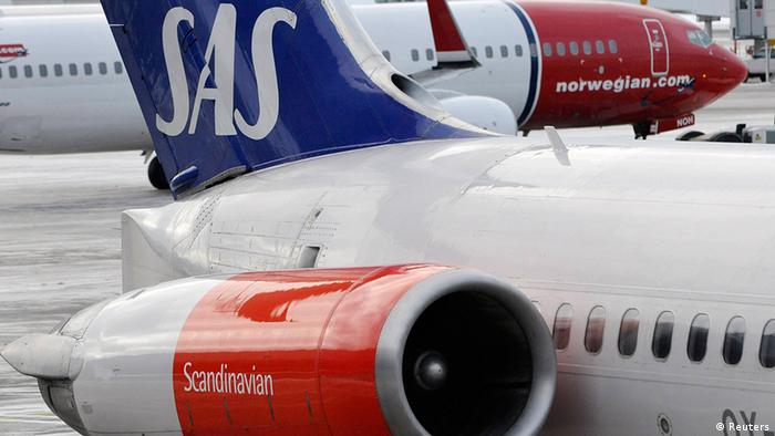 Norwegian Air's Boeing 737-800 aircraft preparing for takeoff behind a SAS MD-82 aircraft parked at gate on Terminal 5 at Arlanda airport, north of Stockholm REUTERS/Johan Nilsson/Scanpix/Files