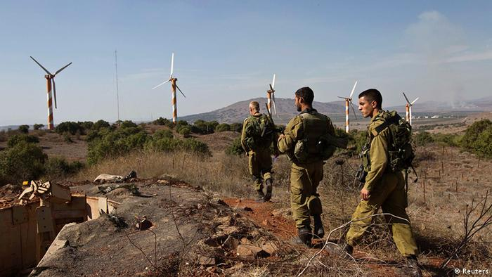 Israeli soldiers walk in front of wind turbines near Alonei Habashan close to the Israeli-Syrian border in the Golan Heights November 4, 2012. Three Syrian tanks entered the demilitarised zone in the Golan Heights between Israel and Syria on Saturday, an Israeli military spokeswoman said. Israeli media said the tanks were involved in fighting rebels trying to overthrow Syrian President Bashar al-Assad. REUTERS/Nir Elias (POLITICS CIVIL UNREST MILITARY)