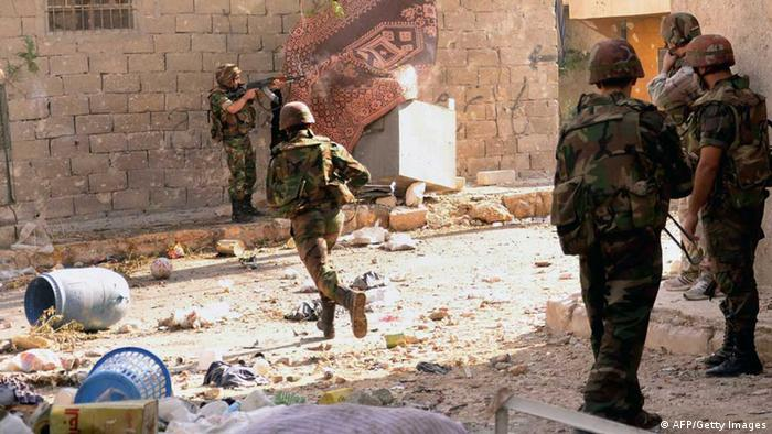 A Syrian army soldier runs across the street as others open fire during clashes with opposition fighters in the Tal al-Zarazi neighbourhood of the northern Syrian city of Aleppo on November 13, 2012. The army shelled rebel positions in the southern province of Daraa, in the central province of Homs, in Idlib in the northwest and in the northern city of Aleppo, the Syrian Observatory for Human Rights said. AFP PHOTO / STR (Photo credit should read STR/AFP/Getty Images)