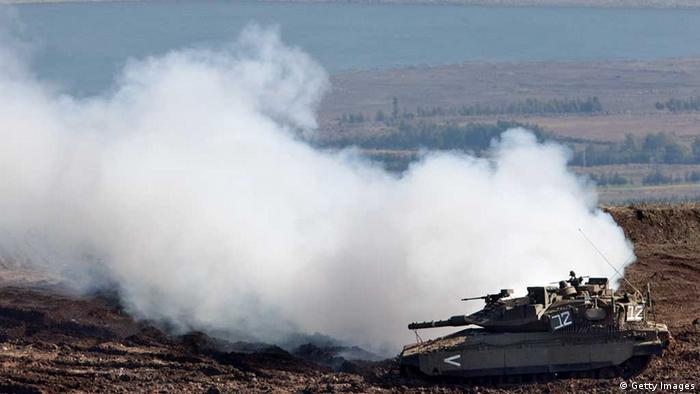 GOLAN HEIGHTS - NOVEMBER 13: (ISRAEL OUT) An Israeli Merkava tank releases white smoke as it maneuvers on the border line with Syria at the Israeli-annexed Golan Heights, overlooking the Syrian village of Breqa on November 13, 2012 in the Golan Heights. Tension remains high in the disputed Golan Heights after Israeli Defence Forces retaliated after mortar shells were fired into Israeli territory from Syria. (Photo by Uriel Sinai/Getty Images)