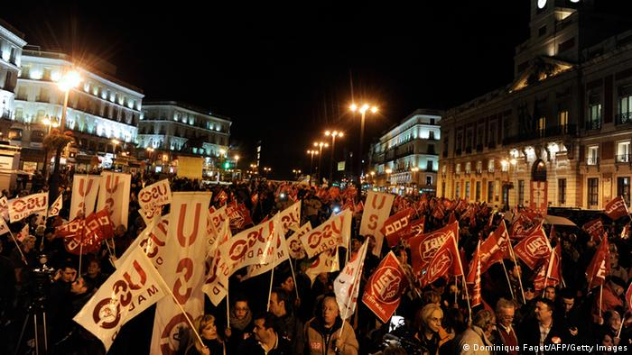 Members of the Workers' Trade Unionist Federation (USO), the Comisiones Obreras trade union (CCOO) and the General Union of Workers (UGT) wave banner as they gather at the Puerta del Sol in Madrid on November 13, 2012, on the eve of a general strike.Spain, the eurozone's fourth-largest economy where one in four workers is unemployed in a deep recession, is calling its second general strike in eight months to protest draconian budget cuts. Spain's main CCOO and UGT unions urged people to rally under slogans such as 'They are taking away our future!', deploying pickets during the night at airports, bus and railway stations. AFP PHOTO / DOMINIQUE FAGET (Photo credit should read DOMINIQUE FAGET/AFP/Getty Images)