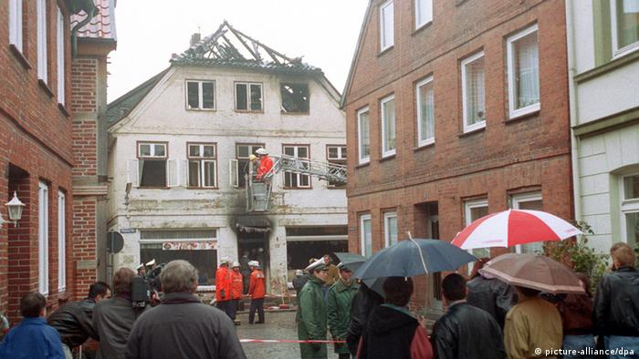 The burnt out shell of a white German house is observed by dozens of spectators standing behind a police line. (Photo: dpa)