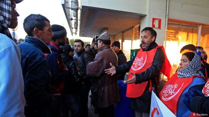 Workers (R) wearing vests bearing the words general strike, form a picket line as they argue with non-striking colleagues (L) reporting for work, at the entrance of Mitrena shipyard, south of Lisbon November 14, 2012. Spanish and Portuguese workers will stage the first coordinated general strike across the Iberian Peninsula on Wednesday, shutting transport, grounding flights and closing schools to protest against spending cuts and tax hikes. REUTERS/Jose Manuel Ribeiro (PORTUGAL - Tags: POLITICS CIVIL UNREST BUSINESS EMPLOYMENT MARITIME TRANSPORT)