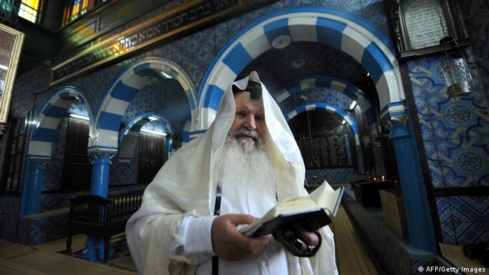 Israeli Rabbi Maimoun, 67, from Tel Aviv and born in Tunis, reads the Torah in the Ghriba Synagogue on April 29, 2010 on the eve of the Jewish annual pilgrimage in Djerba. This week marks the eight anniversary of the suicide bombing that racked this sleepy island resort, desecrating an ancient synagogue and killing 21 people. More than 6,000 Jewish pilgrims are expected including 1,500 Israelis on May 22/23, in a rare pilgrimage to an Arab land. AFP PHOTO/ FETHI BELAID (Photo credit should read FETHI BELAID/AFP/Getty Images)