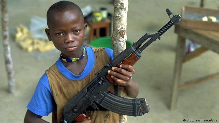 A 12 year old boy displays his Kalashnikov rifle during the civil war in Sierra Leone