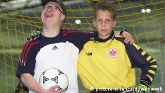 A young boy and a young boy with down syndrome play soccer together