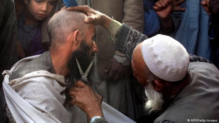 KABUL, AFGHANISTAN: Street hairdresser cuts a man's beard 13 November 2001 in Kabul, after Northern Alliance soldiers captured the capital. A few hours after opposition forces poured into Kabul, many men cut their beards as it was forbidden during the Taliban regime. Taliban spiritual leader Mullah Mohammad Omar has fled Afghanistan for Pakistan, RIA Novosti quoted a senior Northern Allliance official as saying Tuesday in neighboring Tajikistan. AFP PHOTO/ Alexander NEMENOV (Photo credit should read ALEXANDER NEMENOV/AFP/Getty Images)
