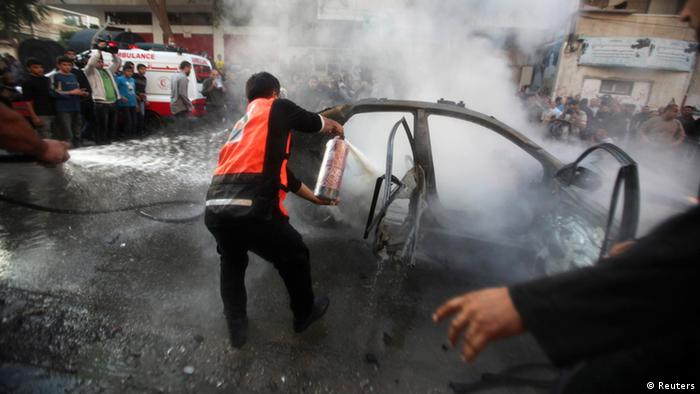 Palestinians extinguish the fire after an Israeli air strike on a car in Gaza City November 14, 2012. An Israeli official said on Wednesday the assassination of Hamas's top commander in the Gaza Strip was not the end of Israel's assault on the coastal territory and more strikes would follow. Ahmed Al-Jaabari, Hamas's military chief, was killed when his car was hit by an Israeli airstrike. Multiple other Israeli attacks rocked the Gaza Strip. REUTERS/Ali Hassan (GAZA - Tags: POLITICS CIVIL UNREST)