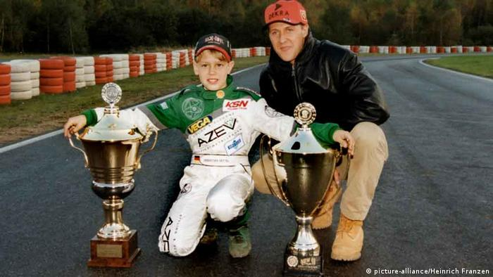 Michael Schumacher kneels beside a young Sebastian Vettel in 1999, awarding him two karting trophies at the Kerpen kart track owned by the Schumacher family