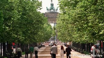 People walking along Berlin's grand Unter den Linden avenue with the Brandenburg Gate at the end