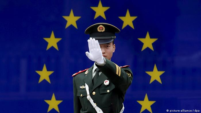 A Chinese paramilitary police officer reacts to having his photograph taken in front of the image of the European Union (EU) flag at the EU embassy in Beijing, China (Photo: EPA/MICHAEL REYNOLDS +++(c) dpa - Bildfunk)