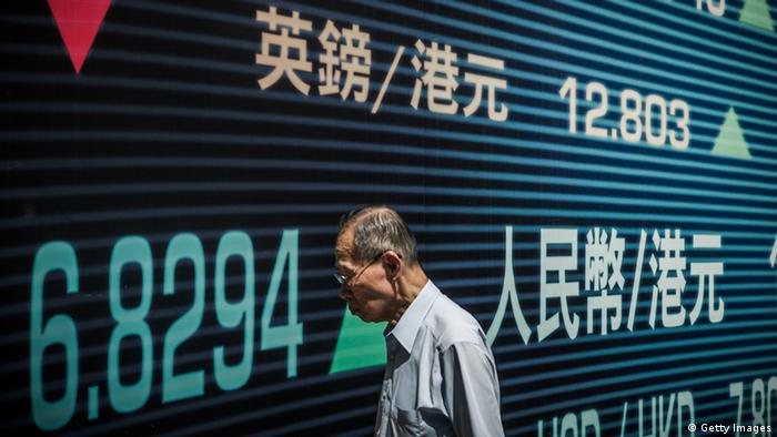 A man walks past a billboard of a bank advertising financial services in Hong Kong