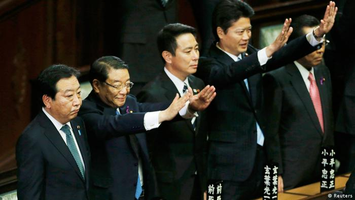 Japan's Prime Minister Yoshihiko Noda (L) stands next to his Cabinet ministers raising their hands and shouting banzai (cheers) after the dissolution of the lower house was announced at the Parliament in Tokyo (Photo: REUTERS/Kim Kyung-Hoon)