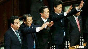 Japan's Prime Minister Yoshihiko Noda (L) stands next to his cabinet ministers raising their hands and shouting banzai (cheers) after the dissolution of the lower house was announced at the Parliament in Tokyo November 16, 2012. (Photo: REUTERS/Kim Kyung-Hoon)