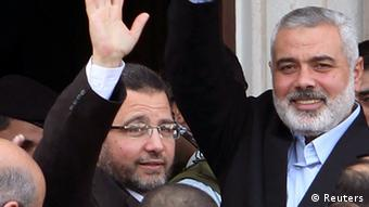 Egyptian Prime Minister Hisham Kandil (L) and senior Hamas leader Ismail Haniyeh wave to people in Gaza City November 16, 2012. Rockets fired from Gaza hit several sites in southern Israel on Friday shortly after Kandil arrived in the Palestinian enclave. REUTERS/Ahmed Zakot (GAZA - Tags: POLITICS CIVIL UNREST)