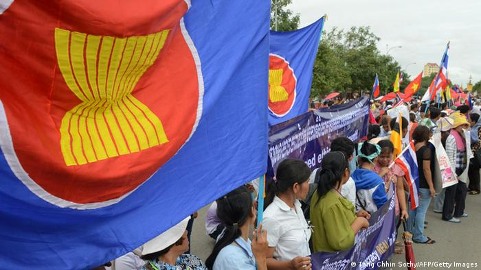 Cambodian people hold flags of Association of Southeast Asian Nations (ASEAN), banners and placards during a protest in front of the National Assembly building in Phnom Penh on November 16, 2012. US President Barack Obama is set to wade into the troubled waters of Asia's maritime disputes at a regional summit next week, with allies hoping for support in their efforts to contain China. AFP PHOTO/ TANG CHHIN SOTHY (Photo credit should read TANG CHHIN SOTHY/AFP/Getty Images)