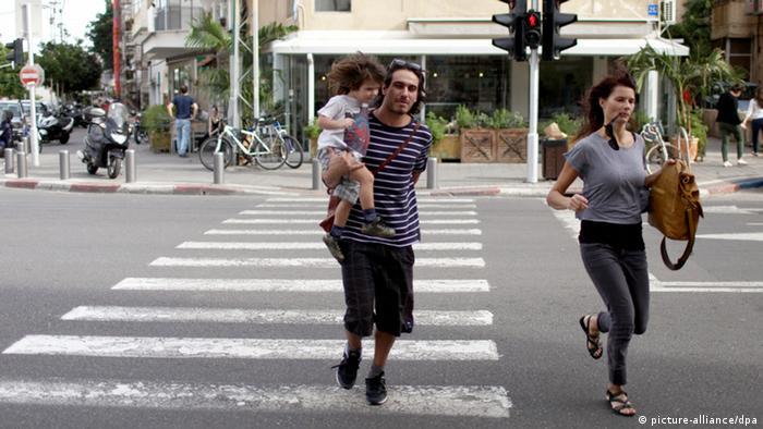 Ein israelisches Paar rennt mit seinem Sohn von der Straße, als in Tel Aviv am 16.11.2012 die Sirenen ertönen. (Foto: EPA)