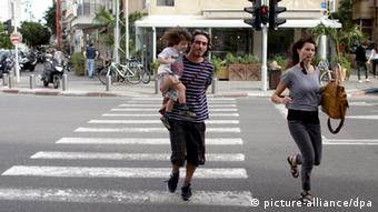 epa03473593 Israeli couple and their son run for cover as a siren sounds in Tel Aviv on 16 November 2012. Two rockets were fired from Gaza towards Tel Aviv today and landed in an open area. today and yesterday is the first time after 21 years from the Gulf War that a real time siren sounds in Tel Aviv EPA/ABIR SULTAN