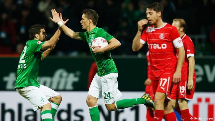 BREMEN, GERMANY - NOVEMBER 18: Nils Petersen (2nd L) of Bremen celebrates with his team mate Sokratis Papastathopoulos after scoring his team's first goal during the Bundesliga match between SV Werder Bremen and Fortuna Duesseldorf at Weser Stadium on November 18, 2012 in Bremen, Germany. (Photo by Joern Pollex/Bongarts/Getty Images)