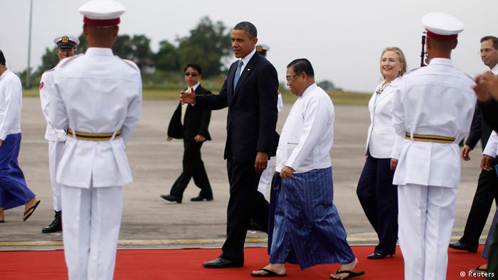 U.S. President Barack Obama is presented with a bouquet of flowers by a girl upon his arrival at Yangon International Airport November 19, 2012. Obama has become the first serving U.S. president to visit Myanmar, arriving on Monday for a trip that will attempt to strike a balance between praising the government's progress in shaking off military rule and pressing it for further reforms. U.S. Secretary of State Hillary Clinton (R) walks behind Obama. REUTERS/Jason Reed (MYANMAR - Tags: POLITICS)