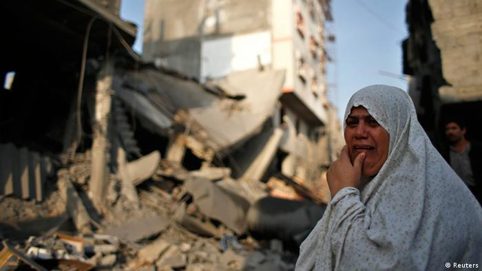 A Palestinian woman reacts in front of a destroyed house after an Israeli air strike in Gaza City November 19, 2012. Hostilities between Islamist militants and Israel entered a sixth day on Monday as diplomatic efforts were set to intensify to try to stop rocket fire from the Gaza Strip and Israeli air strikes on Gaza. International pressure for a ceasefire seemed certain to mount after the deadliest single incident in the flare-up on Sunday claimed the lives of at least 11 Palestinian civilians, including four children. REUTERS/Mohammed Salem (GAZA - Tags: MILITARY POLITICS CONFLICT)