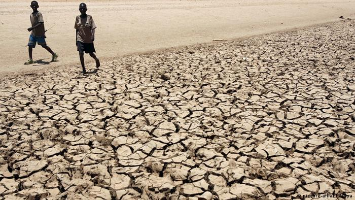 People walking on dried, cracked earth Photo: +++(c) dpa - Bildfunk+++
