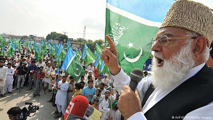 Qazi Hussain Ahmad (R), chief of the Pakistani fundamentalist party Jamaat-e-Islami (JI), addresses a rally in Lahore on August 31, 2008 to condemn atrocities in Indian-controlled Kashmir. The JI organized a rally to express solidarity with Muslims in Jammu said to be under threat by Hindu fanatics in Indian-held Kashmir. Hindus in Indian Kashmir on August 31 suspended protests after the government agreed to temporarily provide land to a Hindu trust managing a key pilgrimage in the Muslim-majority region. AFP PHOTO/Arif ALI (Photo credit should read Arif Ali/AFP/Getty Images)