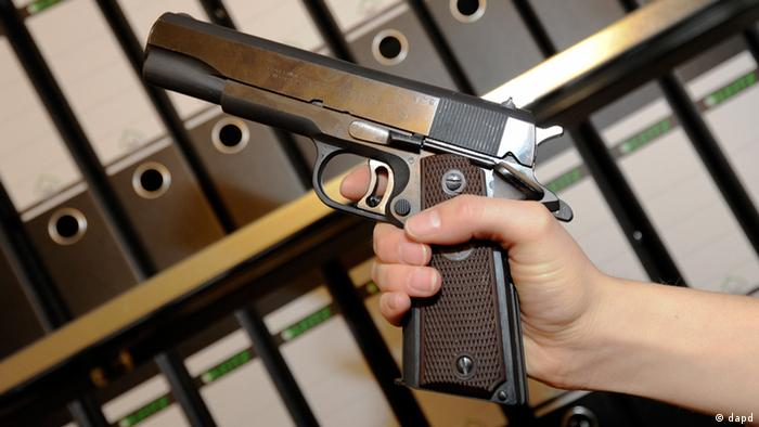 A close-up of a handgun, held in front of an array of files