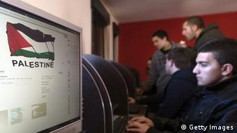 Palestinian youths check their facebook accounts at an internet cafe