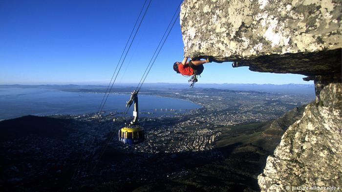 Ein junger Mann beim Klettern in den Bergen.