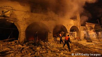 Palestinian firefighters try to extinguish a blaze after an Israeli air strike on the Islamic National Bank building in Gaza City on November 20, 2012. Israeli leaders discussed an Egyptian plan for a truce with Gaza's ruling Hamas, reports said, before a mission by the UN chief to Jerusalem and as the toll from Israeli raids on Gaza rose over 100. AFP PHOTO/MAJDI FATHI (Photo credit should read MAJDI FATHI/AFP/Getty Images)