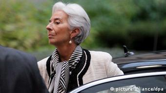 A gray-haired woman wearing a white blazer and a black and white scarf steps out of a black automobile (Photo: EPA/OLIVIER HOSLET)