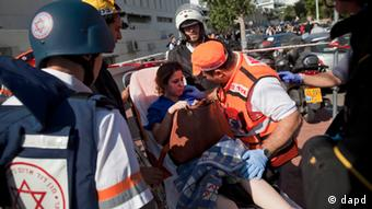 Israeli rescue workers and paramedics carry an injured woman from the site of a bombing in Tel Aviv (photo:Oded Balilty/AP/dapd)