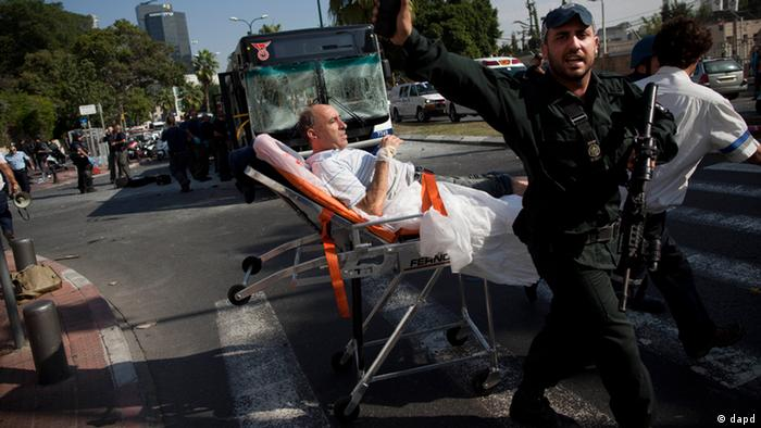 Israeli rescue workers and paramedics carry a wounded person from the site of a bombing in Tel Aviv, Israel, Wednesday, Nov. 21, 2012. A bomb ripped through an Israeli bus near the nation's military headquarters in Tel Aviv on Wednesday. Photo:Oded Balilty/AP/dapd
